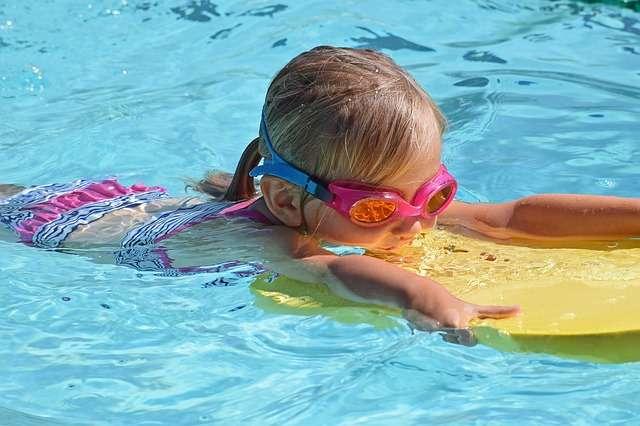 Bambina in piscina con la tavoletta